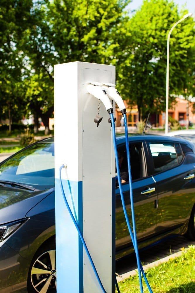 Puesto con mangueras de recarga eléctrica para vehículos electricos en ciudad